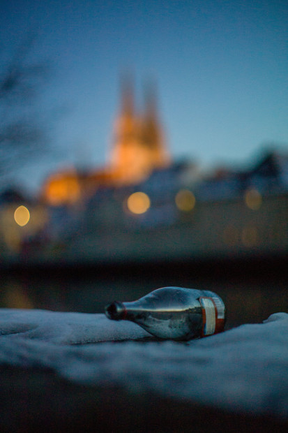 Bottle On Wall With Blurred Building In Background