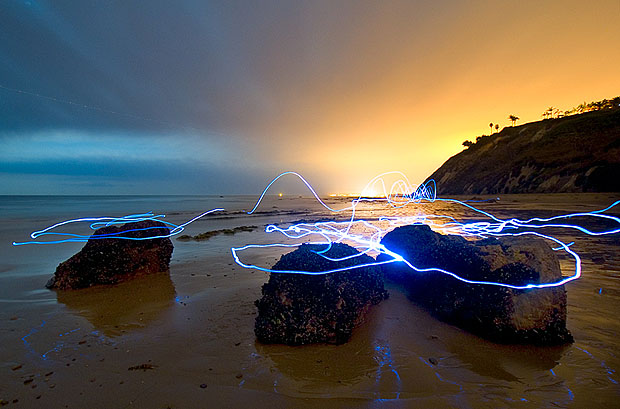 Light streaks around rocks on a beach at sunset