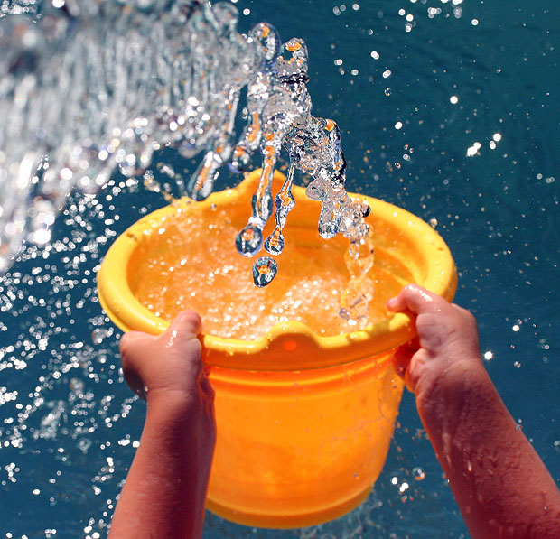 Water filling an orange bucket