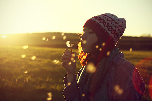 Girl blowing a dandelion at sunset