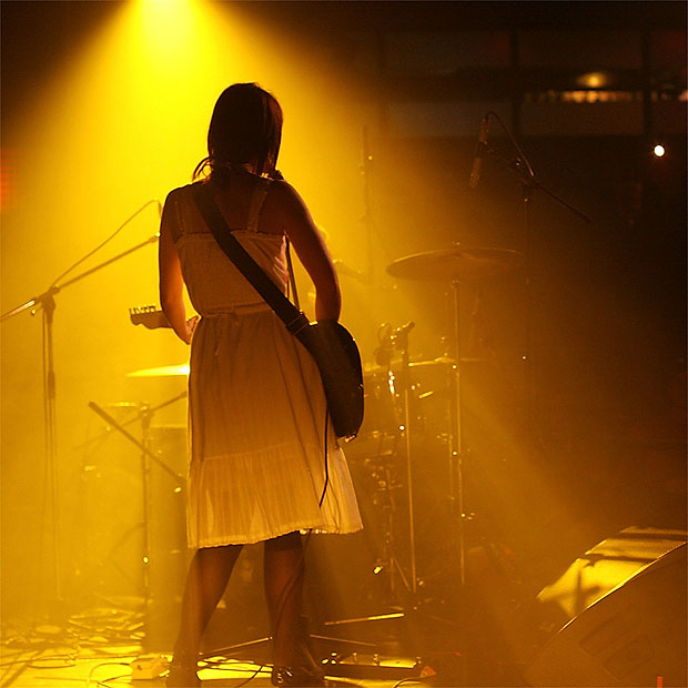 Female guitarist lit in yellow