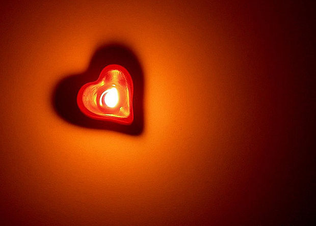 Candle casting a heart shaped shadow