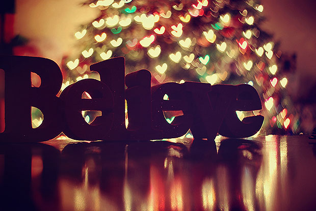 Believe statue in front of Christmas tree bokeh