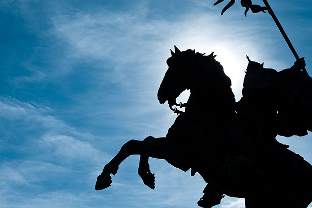 Horse statue silhouetted against a blue sky