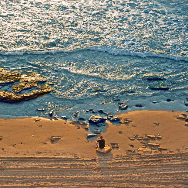 Man sitting on beach photographed from above