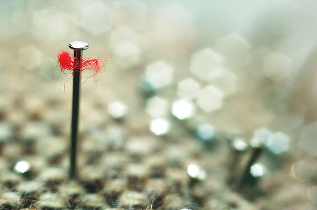 Close up of a needle with a piece of red thread