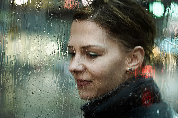 Woman behind glass with rain running down it