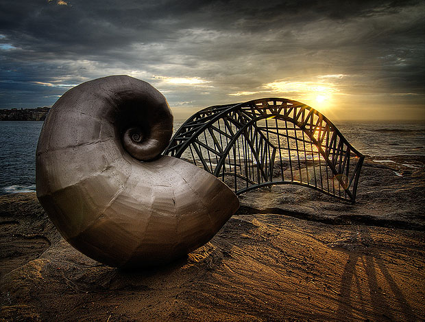 Shell and bridge sculpture by the sea at sunset