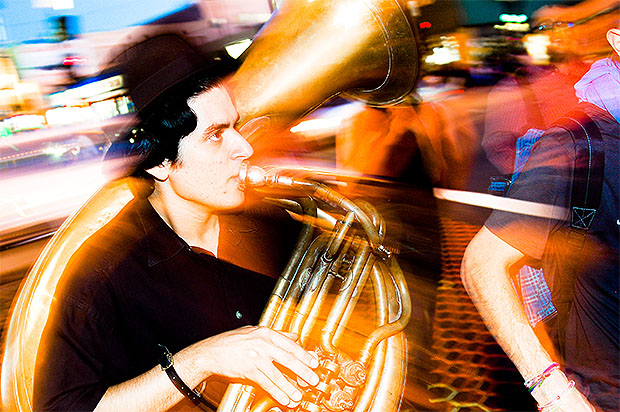 Slow sync flash photo of a man playing a French horn