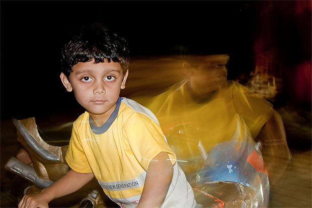 Slow sync flash photo of a boy on a bike at night