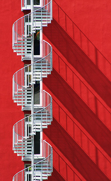 Spiral stairs against a red wall with long shadows
