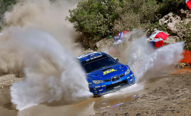 Subaru rally car racing through water
