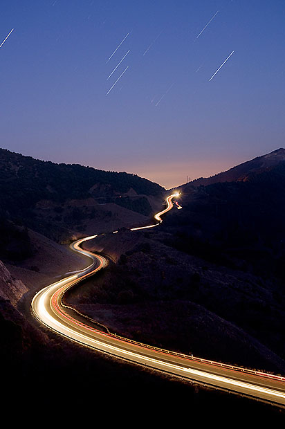 A winding road with car light trails